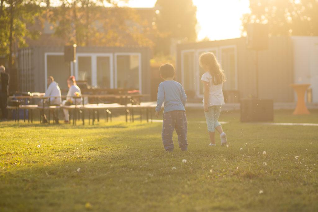 open air location berlin kinder stehen auf wiese und gucken die Eltern an