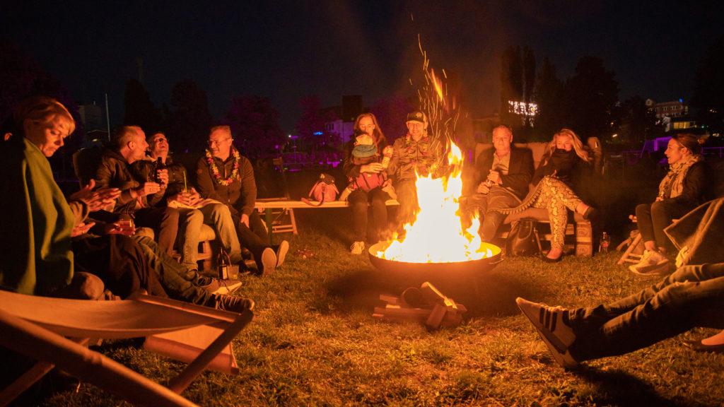 open air location berlin menschen sitzt im dunklen um eine Feuerschale