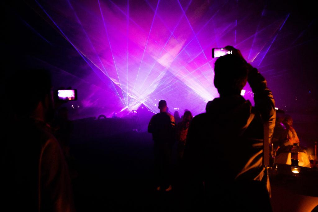 open air location berlin Lila lasershow wird aufgenommen von Mann mit Handy