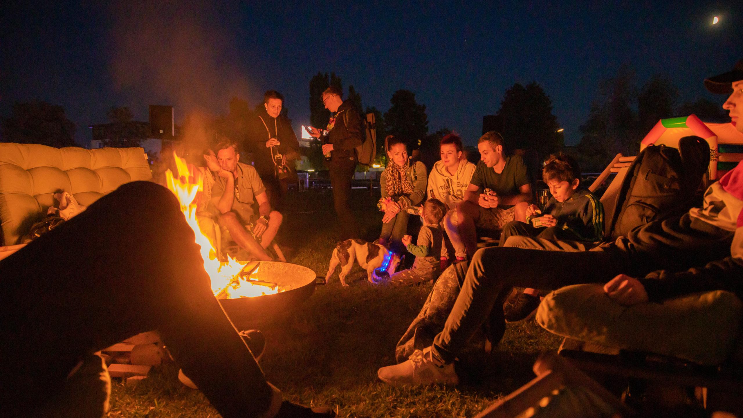 outdoor event eine Gruppe Menschen sitzt neben einem Lagerfeuer